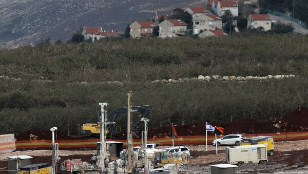 In this Thursday, Dec. 13, 2018 photo, Israeli military equipment works on the Lebanese-Israeli border in front of the Israeli town of Metula, background, near the southern village of Kafr Kila, Lebanon. As Israeli excavators dig into the rocky ground, Lebanese across the frontier gather to watch what Israel calls the Northern Shield operation aimed at destroying attack tunnels built by Hezbollah. But Lebanese soldiers in new camouflaged posts, behind sandbags, or inside abandoned homes underscore the real anxiety that any misstep could lead to a conflagration between the two enemy states that no one seems to want. - Sputnik International