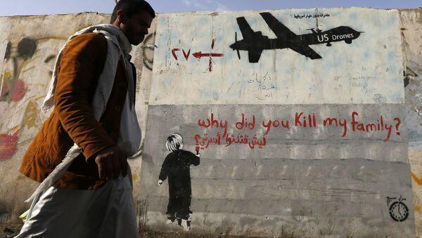 A man walks past a graffiti, denouncing strikes by U.S. drones in Yemen, painted on a wall in Sanaa, Yemen on November 13, 2014 - Sputnik International