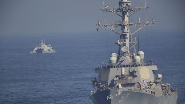 The USS Mitscher, part of a strike group led by the USS John C. Stennis aircraft carrier, sails as an Iranian Revolutionary Guard vessel shadows it on Friday, Dec. 21, 2018. - Sputnik International