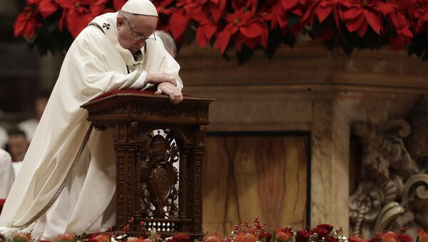 Pope Francis kneels on the altar as he celebrates the Christmas Eve Mass in St. Peter's Basilica at the Vatican, Monday, Dec. 24, 2018 - Sputnik International
