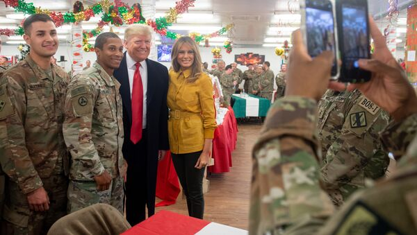 US President Donald Trump and First Lady Melania Trump take photos with members of the US military during an unannounced trip to Al Asad Air Base in Iraq on December 26, 2018 - Sputnik International