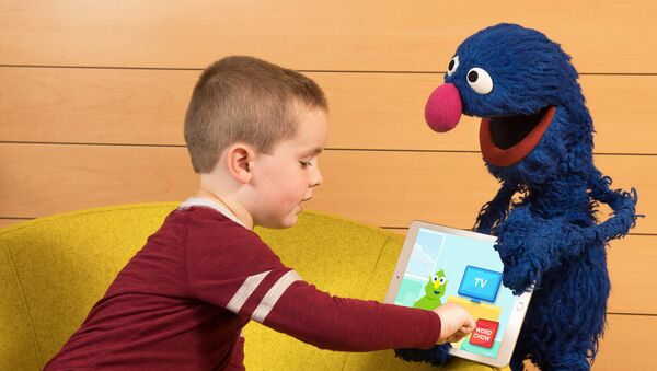 In this photo taken by Feature Photo Service for IBM: A child shows his friend Grover the new cognitive vocabulary learning app from IBM and Sesame Workshop. The app was recently piloted in Gwinnett County Public School System in Georgia to enhance students' vocabulary development. - Sputnik International