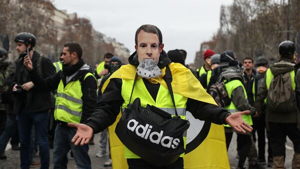 A protestor wearing a yellow vest (gilet jaune) and with a French President Emmanuel Macron mask poses on the Champs Elysees avenue in Paris on December 8, 2018 during protest against rising costs of living they blame on high taxes. - Sputnik International