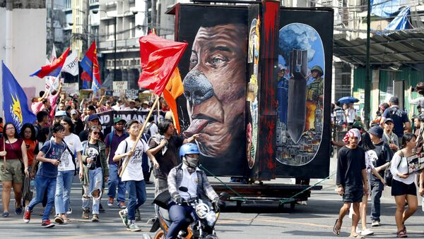 Protesters march with a rotating effigy of Philippine President Rodrigo Duterte for a rally near the Presidential Palace to mark the UN Declaration of International Human Rights Day Monday, Dec. 10, 2018 in Manila, Philippines. The protesters accuse the President of alleged rampant human rights violations since taking office more than two years ago - Sputnik International