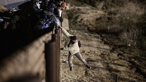A migrant jumps the border fence to get into the U.S. side to San Diego, Calif., from Tijuana, Mexico, Tuesday, Jan. 1, 2019 - Sputnik International
