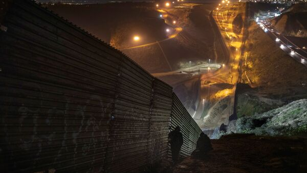 Migrants look for a place to jump the border fence to get into the U.S. side to San Diego, Calif., from Tijuana, Mexico, Saturday, Dec. 29, 2018 - Sputnik International