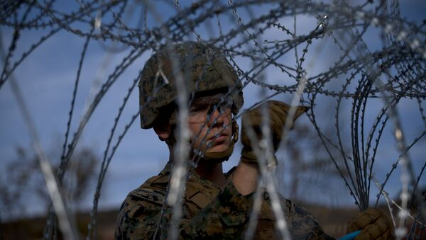 A soldier agent sets up barbed wire at the San Ysidro port of entry, at the U.S.-Mexico border, seen from Tijuana, Mexico, Thursday, Nov. 22, 2018 - Sputnik International