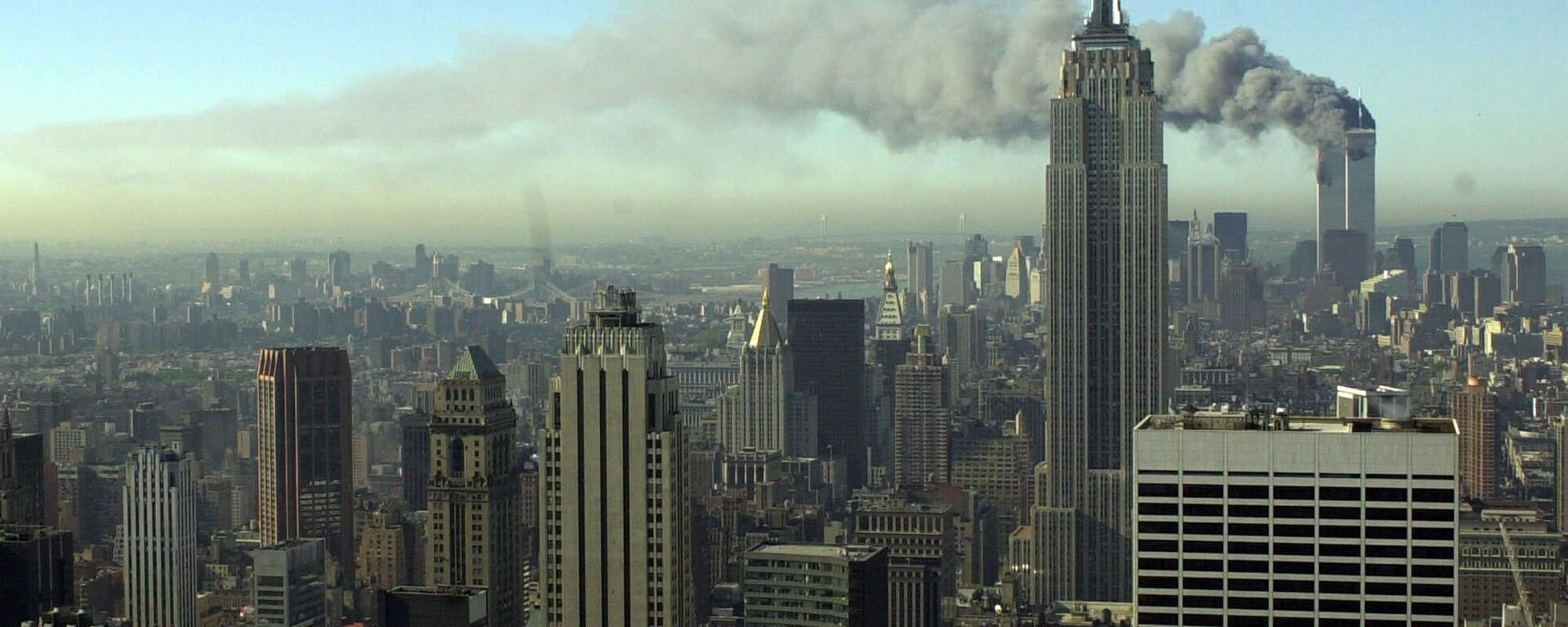 Plumes of smoke pour from the World Trade Center buildings in New York Tuesday, Sept. 11, 2001. Planes crashed into the upper floors of both World Trade Center towers minutes apart Tuesday in a horrific scene of explosions and fires that left gaping holes in the 110-story buildings - Sputnik International, 1920, 16.04.2020