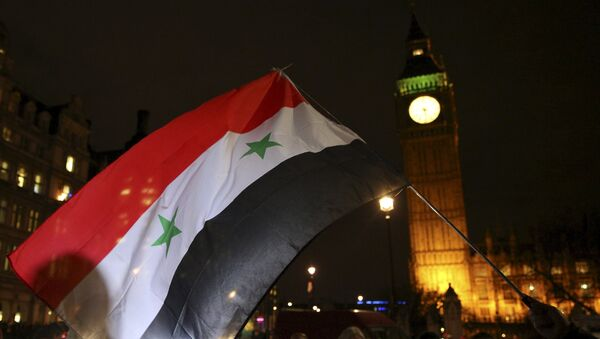 Anti-war protesters wave a Syrian flag as they demonstrate against proposals to bomb Syria outside the Houses of Parliament in London, Britain December 1, 2015. - Sputnik International