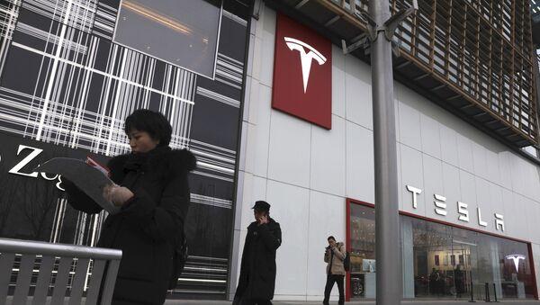 Residents walk past a Tesla store in Beijing - Sputnik International