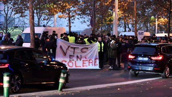 Demonstrator wearing yellow vests (Gilet jaune) hold banners reading angry VTC (Vehicle for Transport with Driver) during a protest against the rising of the fuel and oil prices on November 17, 2018 near Bercy Finance Ministry in Paris - Sputnik International