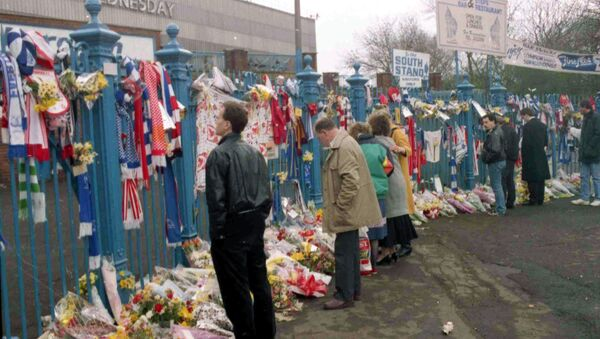 People looking at the hundreds of scarves and flowers which were left in tribute at Hillsborough in the aftermath of the disaster - Sputnik International