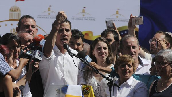 Juan Guaido, president of National Assembly, shows marks on his wrists, which he says are from handcuffs, to supporters at a rally in Caraballeda, Venezuela, Sunday, Jan. 13, 2019. The new head of Venezuela's increasingly defiant congress was pulled from his vehicle and briefly detained by police Sunday, a day after the U.S. backed him assuming the presidency as a way out of the country's deepening crisis. Guaido's wife Fabiana Rosales stands next to him, right. (AP Photo/Fernando Llano) - Sputnik International