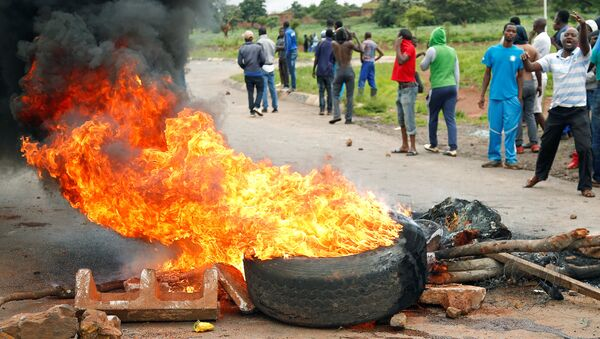Protesters stand behind a burning barricade during protests on a road leading to Harare, Zimbabwe, January 15, 2019 - Sputnik International