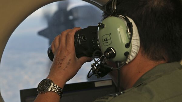 In this March 22, 2014, file photo, Flight Officer Jack Chen uses binoculars at an observers window on a Royal Australian Air Force P-3 Orion during the search for missing Malaysia Airlines Flight MH370 in Southern Indian Ocean, Australia - Sputnik International