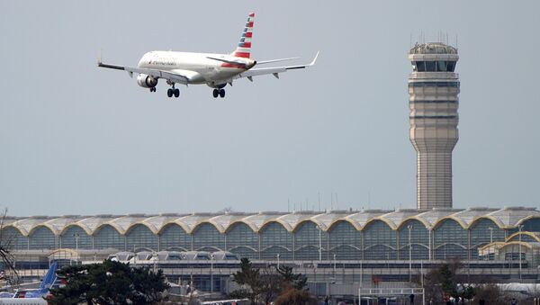 An airplane flies past the tower where air traffic controllers work despite not receiving their paychecks, on the 22nd day of a partial government shutdown at Reagan National Airport in Washington, U.S., January 12, 2019 - Sputnik International