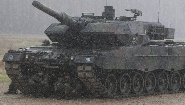 Polish troops take shelter from pouring rain under the belly of a tank during a ceremony welcoming a deployment of new NATO troops in Orzysz, northeast Poland - Sputnik International