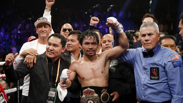Manny Pacquiao's hand is raised after he retained the WBA world welterweight title on 19 January 2019 - Sputnik International