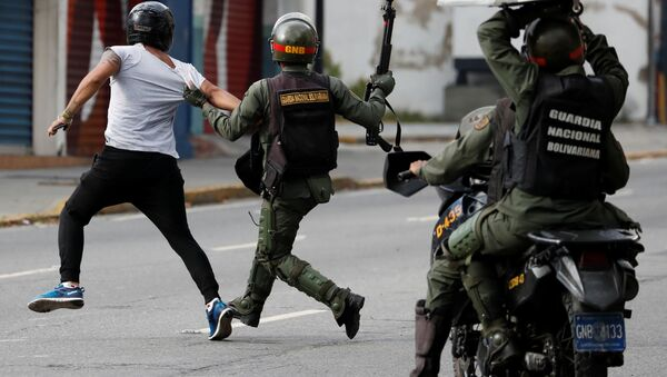 Security forces run after a demonstrator during a protest of opposition supporters against Venezuelan President Nicolas Maduro's government in Caracas, Venezuela - Sputnik International