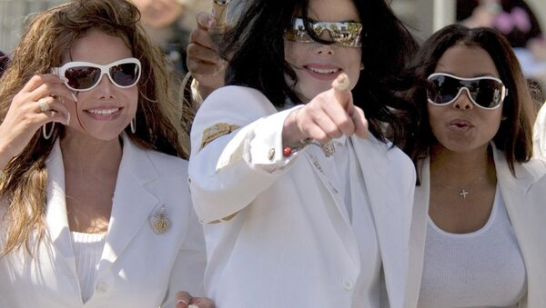 Superstar Michael Jackson (C), flanked by his sisters LaToya Jackson (L) and Janet Jackson (R) acknowledge their fans during a lunch break at a pretrial hearing at the Santa Barbara County Courthouse in Santa Maria, California, 16 August 2004. - Sputnik International