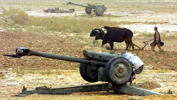 An Afghan peasant ploughs near Soviet-made D-30 howitzers just outside the village of Ai-Khanum, Northern Afghanistan, Friday Nov. 9, 2001. - Sputnik International