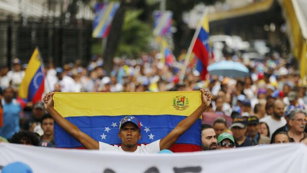 An opposition member holds a Venezuelan national flag during a protest march against President Nicolas Maduro in Caracas, Venezuela, Wednesday, Jan. 23, 2019. - Sputnik International