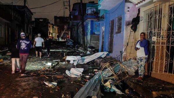 Cubans walk past debris in the tornado-hit Luyano neighbourhood in Havana early on January 28, 2019 - Sputnik International