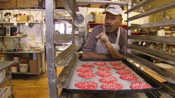 In this Thursday, Jan. 24, 2019, video image provided by KING-TV, baker Ken Bellingham, who owns Edmonds Bakery, speaks during an interview at his shop in Edmonds, Wash. Bellingham is apologizing for a politically charged Valentine's Day cookie that generated an uproar on social media. - Sputnik International