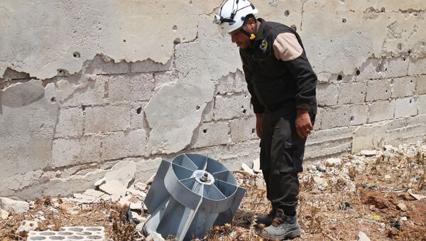 A member of the Syrian civil defence volunteers, also known as the White Helmets, stands next to the tail fin of a bomb as local bomb-disposal experts search for unexploded ordnance in a rebel-held area of Daraa on July 20, 2017 - Sputnik International