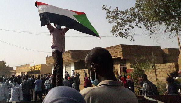 Demonstrators against President al-Bashir hold up a Sudanese flag during protests in Omdurman in January 2019 - Sputnik International