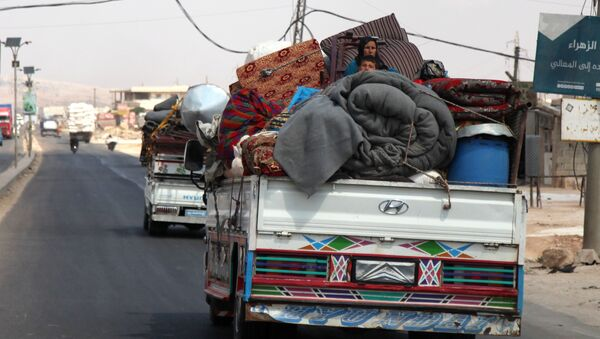 Syrians ride with their belongings in trucks as they head to safer areas in the town of Khan Sheikhun. - Sputnik International