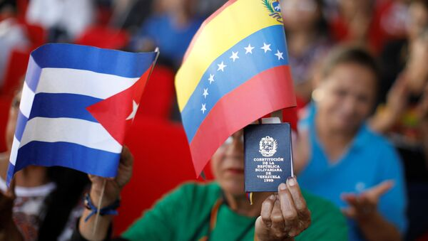 A supporter of Venezuela's President Nicolas Maduro holding a copy of the Venezuelan constitution and flags of Venezuela and Cuba, takes part in a gathering in support of his government outside the Miraflores Palace in Caracas, Venezuela January 26, 2019 - Sputnik International