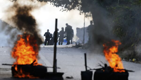 Bolivarian National Police stand behind a burning roadblock set up by anti-government protesters who are showing support for a mutiny by some National Guard soldiers in the Cotiza neighborhood of Caracas, Venezuela, Monday, Jan. 21, 2019 - Sputnik International