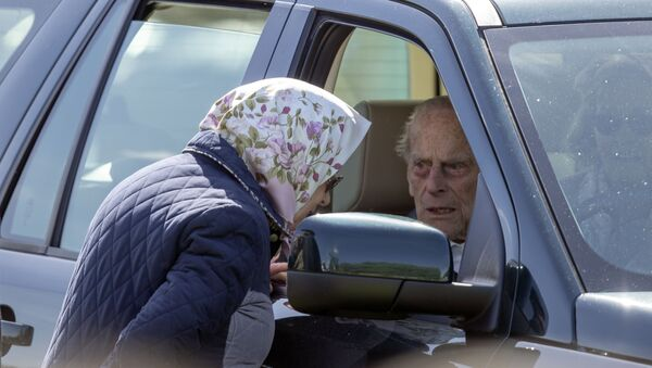 Britain's Prince Philip sits in the driving seat of a car, talking to his wife, Queen Elizabeth II - Sputnik International