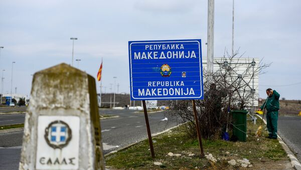 Workers clean up near the sign at the border between Macedonia and Greece, near Gevgelija, on February 11, 2019. - Sputnik International