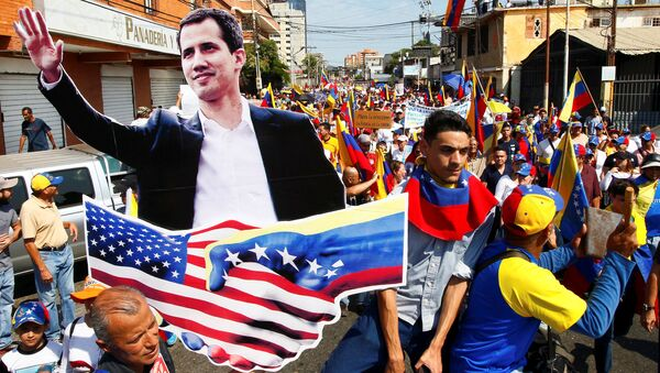 Opposition supporters carrying a cardboard cut-out of Venezuelan opposition leader Juan Guaido take part in a rally against Venezuelan President Nicolas Maduro's government and to commemorate the Day of the Youth in Maracaibo, Venezuela February 12, 2019. - Sputnik International