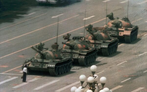 Tank Man blocks a column of Type 59 tanks heading east on Beijing's Chang'an Boulevard (Avenue of Eternal Peace) near Tiananmen Square during the Tiananmen Square protests of 1989. This photo was taken from the sixth floor of the Beijing Hotel, about half a mile away, through a 400 mm lens. The name and fate of the man is unknown - Sputnik International