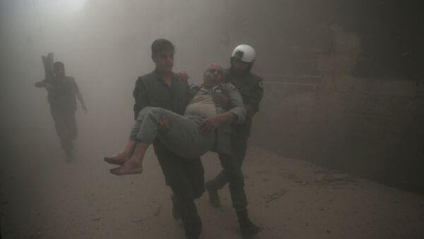 Civil defense members carry an injured man after an air strike in the rebel-held Douma neighbourhood of Damascus, Syria October 12, 2016. - Sputnik International
