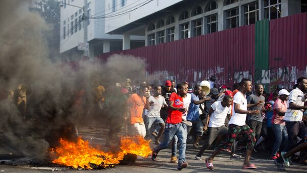 Demonstrators run away during a protest to demand the resignation of President Jovenel Moise and demanding to know how Petro Caribe funds have been used by the current and past administrations, in Port-au-Prince, Haiti, Saturday, Feb. 9, 2019. Much of the financial support to help Haiti rebuild after the 2010 earthquake comes from Venezuela's Petro Caribe fund, a 2005 pact that gives suppliers below-market financing for oil and is under the control of the central government.  - Sputnik International