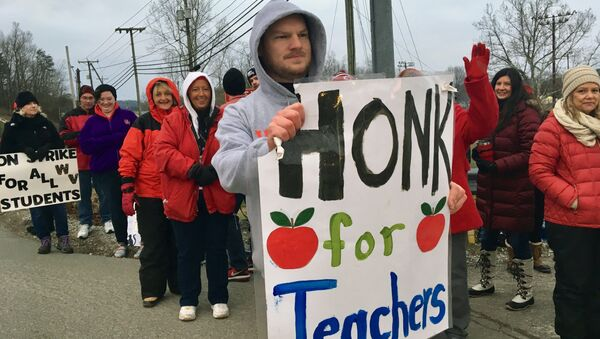 Striking teachers wave at passing cars outside Poca High School Tuesday, Feb. 19, 2019, in Poca, W.Va. Poca is in Putnam County, the only county in the state where public schools were held on the first day of the strike - Sputnik International