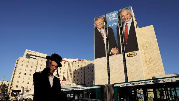 A man walks past a Likud election campaign billboard, depicting U.S. President Donald Trump shaking hands with Israeli Prime Minister Benjamin Netanyahu, in Jerusalem February 4, 2019 - Sputnik International