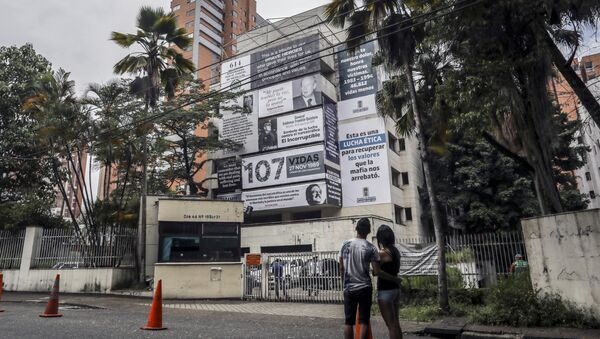 A couple looks at the Monaco building, which was once home to Colombian drug lord Pablo Escobar, as it is covered with pictures of victims of his Medellin Cartel, in Medellin, Colombia, on December 11, 2018 - Sputnik International