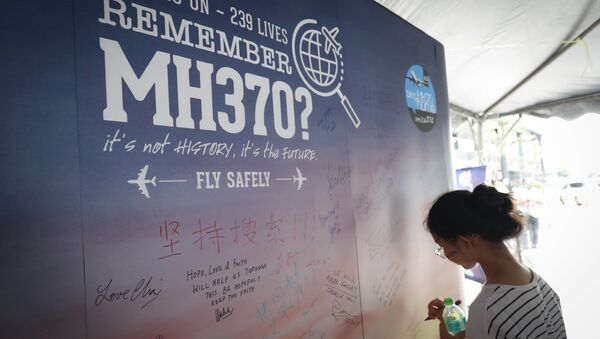A girl writes a condolence message during the Day of Remembrance for MH370 event in Kuala Lumpur, Malaysia.  - Sputnik International