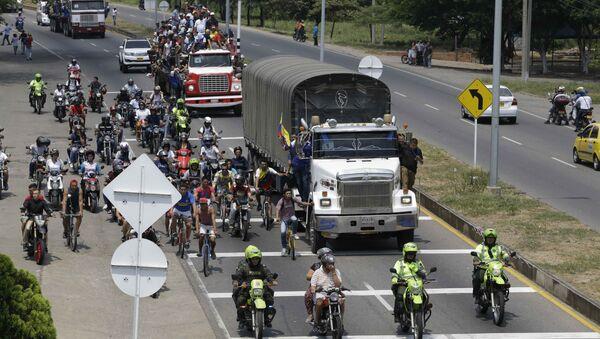 People ride atop and alongside semi-trailers accompanying U.S. humanitarian aid destined for Venezuela, in Cucuta, Colombia, Saturday, Feb. 23, 2019 . - Sputnik International
