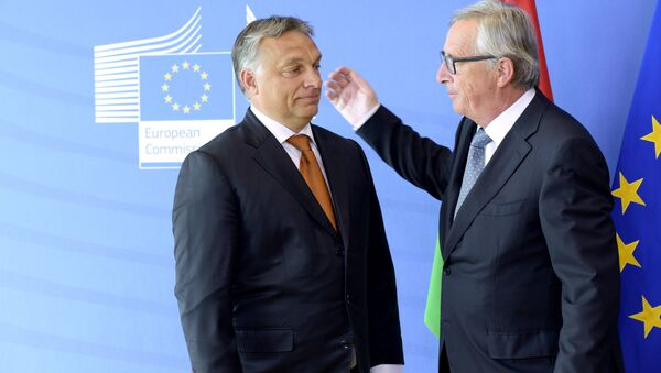 Hungary's Prime Minister Viktor Orban (L) is greeted by European Union Commission President Jean-Claude Juncker of Luxembourg prior to their meeting at the European Union Commission headquarter in Brussels on September 3, 2015 - Sputnik International
