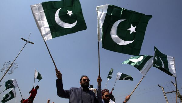 People carry national flags as they celebrate, after Pakistan shot down two Indian military aircrafts, in Lahore, Pakistan February 27, 2019 - Sputnik International