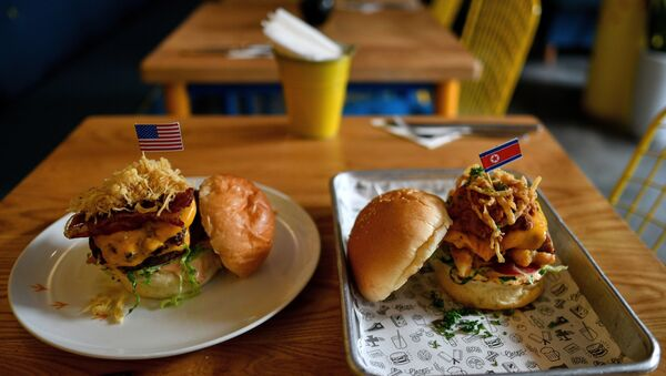 A Dirty Donald burger (L) and a Kim Jong Yum burger (R) is placed on a table at the Durty Bird restaurant in Hanoi on February 21, 2019 - Sputnik International