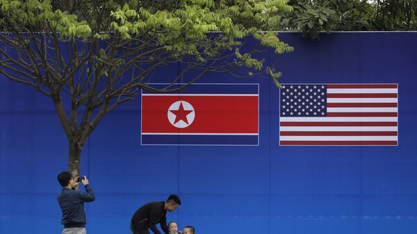 People take pictures in front of a poster featuring the upcoming second summit between the U.S. and North Korea in Hanoi, Vietnam - Sputnik International