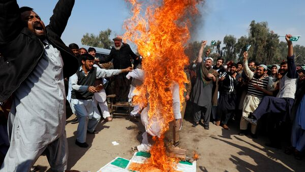 People chant slogans as they burn an effigy depicting Indian Prime Minister Narendra Modi, after Pakistan shot down two Indian military aircrafts, according to Pakistani officials, in Peshawar, Pakistan February 28, 2019 - Sputnik International
