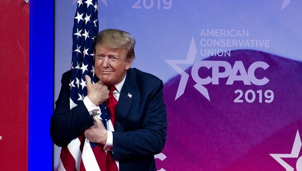 President Donald Trump hugs the American flag as he arrives to speak at Conservative Political Action Conference, CPAC 2019, in Oxon Hill, Md., Saturday, March 2, 2019. - Sputnik International